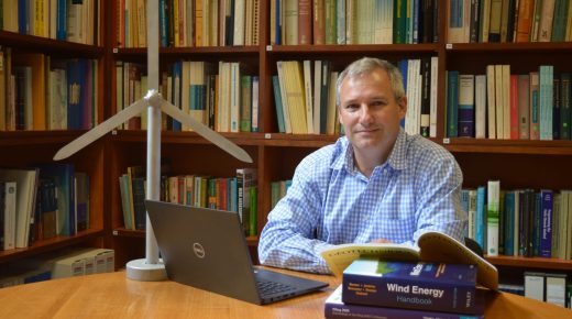 Byron Byrne at a desk with books and a mini wind turbine beside him